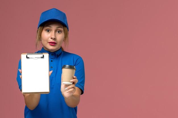 Vorderer blick junger weiblicher kurier in blauer uniform, die tasse kaffee und notizblock hält