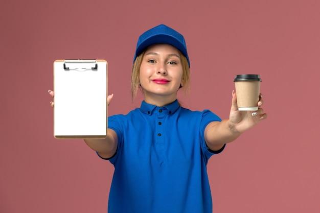 Vorderer blick junger weiblicher kurier in der blauen uniform, die das halten der tasse kaffee und des notizblocks lächelnd, dienstuniformlieferfraufrauenjobarbeiterfarbe aufwirft
