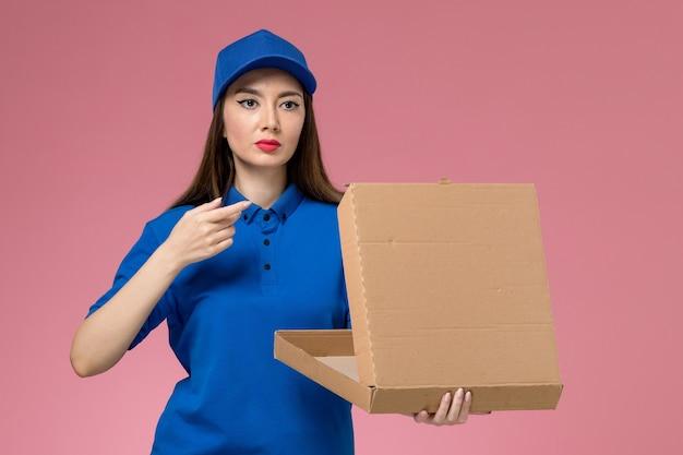 Vorderer blick junger weiblicher kurier in der blauen uniform und im umhang, der leere nahrungsmittellieferbox auf der rosa wand hält