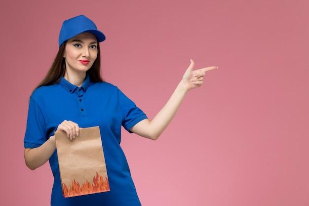 Vorderer blick junger weiblicher kurier in der blauen uniform und im umhang, der papiernahrungsmittelpaket hält, das auf rosa wand aufwirft