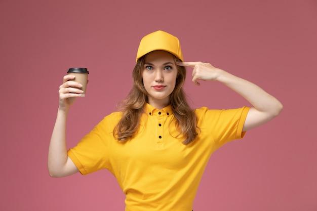Vorderer blick junger weiblicher kurier in der gelben uniform, die lieferkaffee hält und auf dem rosa hintergrundjobuniformlieferdienstarbeiter aufwirft