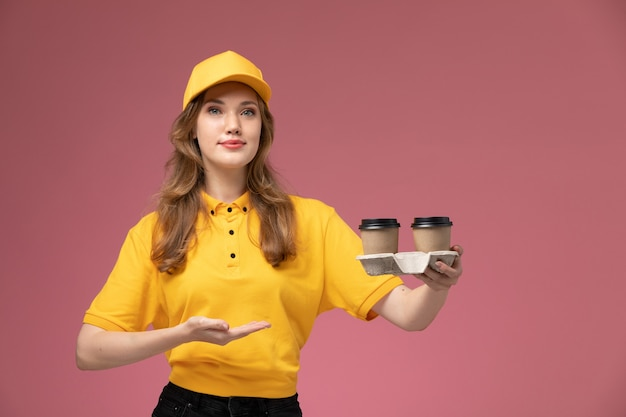 Vorderer blick junger weiblicher kurier in der gelben uniform, die lieferkaffeetassen auf dem rosa hintergrundschreibtischjobuniformlieferdienstarbeiter hält