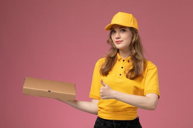 Vorderer blick junger weiblicher kurier in der gelben uniform, die lieferung-nahrungsmittelbox auf dem rosa hintergrundlieferdienstuniform weiblicher arbeiter hält