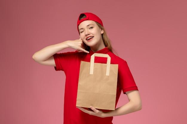Vorderer blick junger weiblicher kurier in der roten uniform, die lieferpapiernahrungsmittelpaket an der hellrosa wand hält