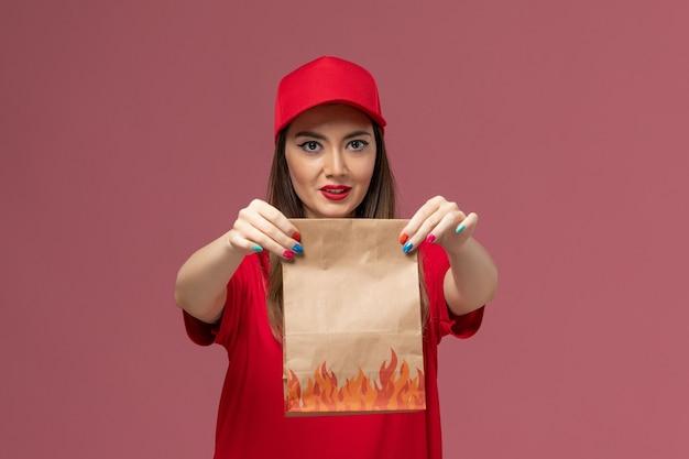Vorderer blick junger weiblicher kurier in der roten uniform, die papiernahrungsmittelpaket auf hellrosa hintergrundarbeiterdienstlieferungsuniform-firmenjob hält