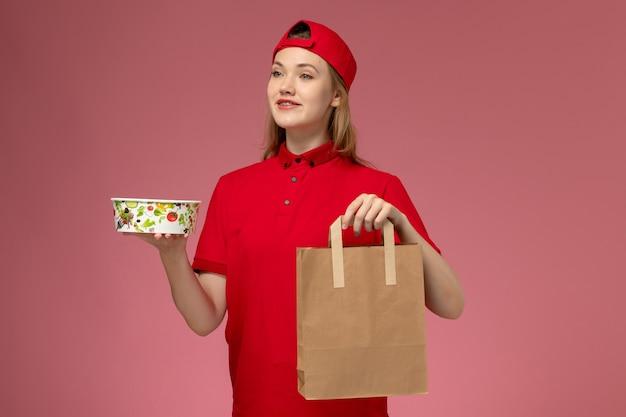 Vorderer blick junger weiblicher kurier in der roten uniform und im umhang, die lieferung nahrungsmittelpaket und schüssel auf rosa wand halten