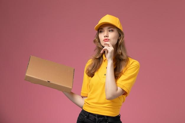 Vorderer blick junger weiblicher kurier in gelbem einheitlichem gelbem umhang, der lebensmittellieferbox auf der dunkelrosa hintergrunduniformuniversitäts-auftragsservicefarbe hält