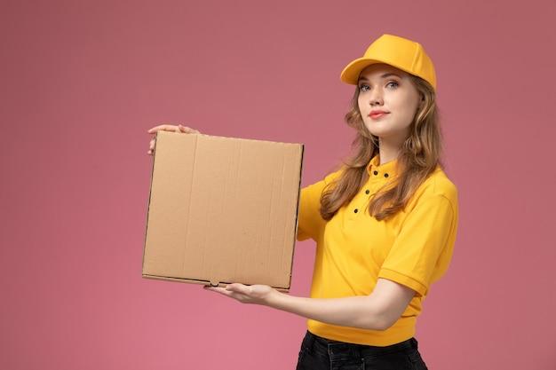 Vorderer blick junger weiblicher kurier in gelbem einheitlichem gelbem umhang, der lebensmittellieferkasten mit leichtem lächeln auf der dunkelrosa schreibtischuniformlieferdienstjobfarbe hält