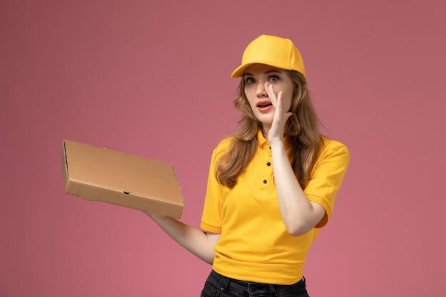 Vorderer blick junger weiblicher kurier in gelbem einheitlichem gelbem umhang, der nahrungsmittellieferbox auf dem dunkelrosa hintergrunduniformlieferdienst weiblicher arbeiter hält