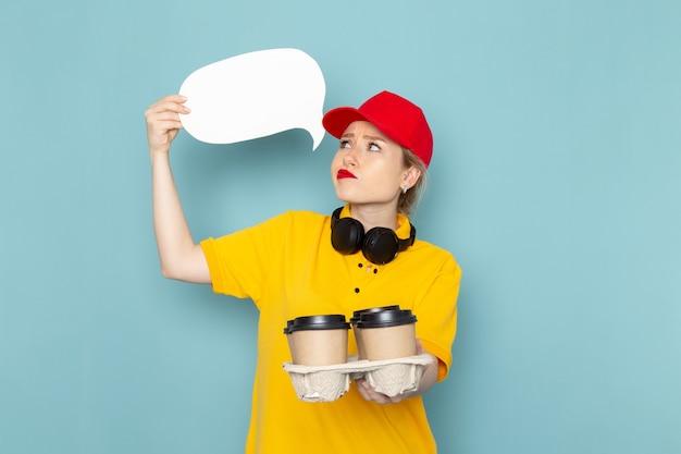 Vorderer blick junger weiblicher kurier in gelbem hemd und rotem umhang, der kaffeetassen und weißes zeichen auf der blauen raumjobarbeit hält