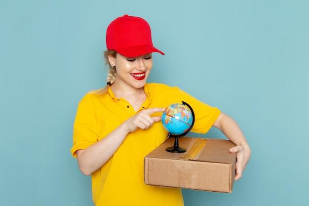 Vorderer blick junger weiblicher kurier in gelbem hemd und rotem umhang, der kleinen globus und paket hält, die auf dem blauen raum lächeln