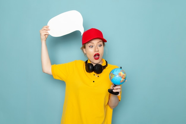 Vorderer blick junger weiblicher kurier in gelbem hemd und rotem umhang, der kleinen globus und weißes zeichen auf der blauen raumarbeit hält