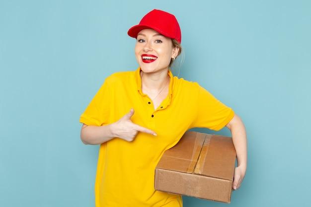 Vorderer blick junger weiblicher kurier in gelbem hemd und rotem umhang, der paket auf dem blauen raumjob lächelt und hält