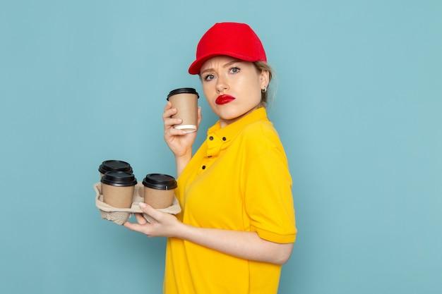 Vorderer blick junger weiblicher kurier in gelbem hemd und rotem umhang, der plastikkaffeetassen auf dem blauen raum hält