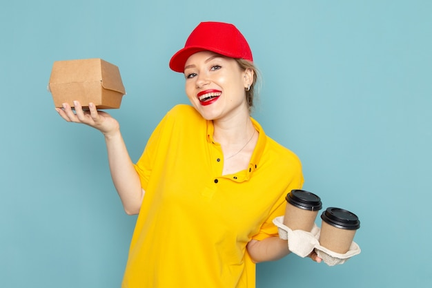 Vorderer blick junger weiblicher kurier in gelbem hemd und rotem umhang, der plastikkaffeetassen und nahrungsmittelpaket auf dem blauen raum hält