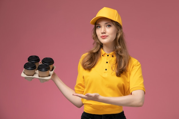 Vorderer blick junger weiblicher kurier in gelber uniform, die kaffeetassen auf dem rosa hintergrundschreibtischjobuniform-lieferservice-arbeiter hält