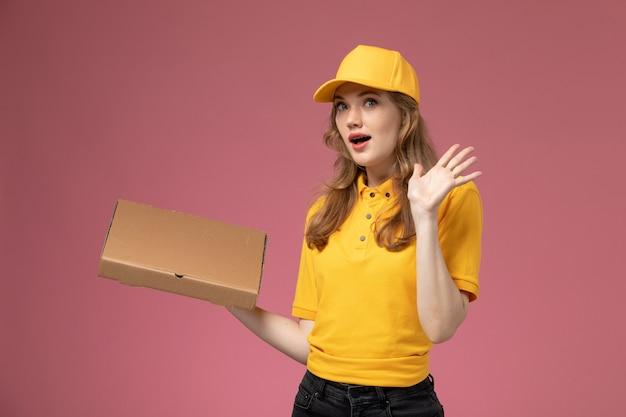 Vorderer blick junger weiblicher kurier in gelber uniform, die lieferpaket mit überraschtem ausdruck auf dem rosa schreibtischjobuniform-lieferservicearbeiter hält