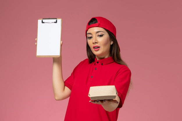 Vorderer blick junger weiblicher kurier in rotem uniformumhang mit wenig liefernahrungsmittelpaket und notizblock auf ihren händen an der rosa wand