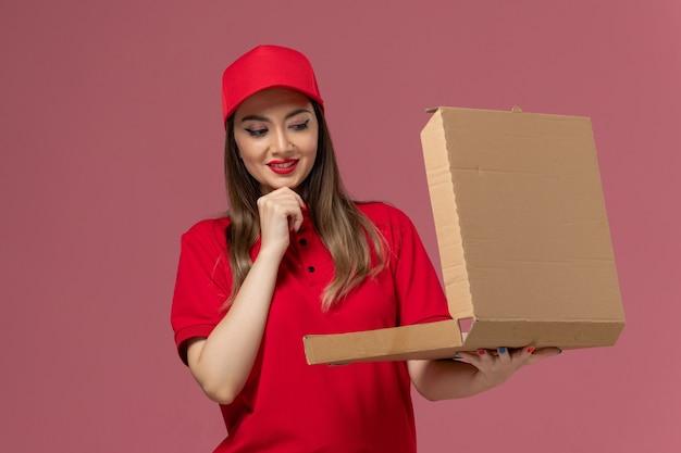 Vorderer blick junger weiblicher kurier in roter uniform, die lieferung food box adn denken auf hellrosa hintergrund service delivery uniform arbeiter firma denkt