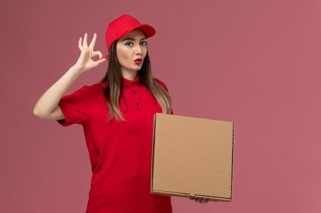 Vorderer blick junger weiblicher kurier in roter uniform, die lieferung food box auf dem rosa hintergrund service delivery uniform company hält