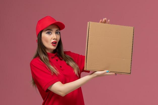 Vorderer blick junger weiblicher kurier in roter uniform, die lieferung food box auf rosa hintergrund service delivery job uniform hält