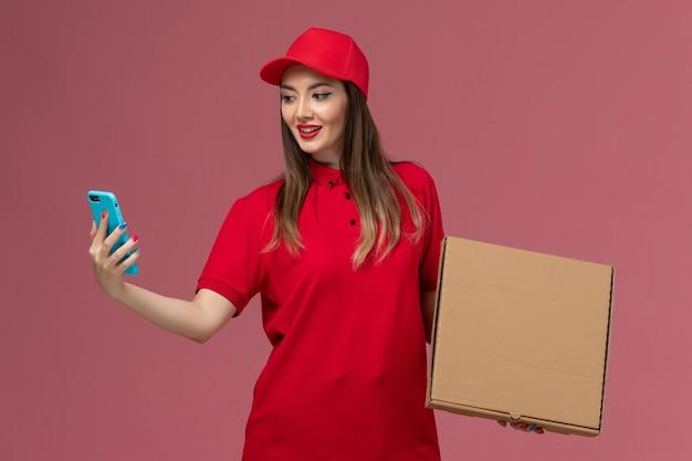 Vorderer blick junger weiblicher kurier in roter uniform, die lieferung nahrungsmittelbox und telefon auf rosa hintergrunddienstlieferuniform hält