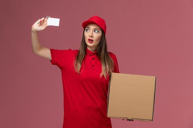 Vorderer blick junger weiblicher kurier in roter uniform, die lieferung nahrungsmittelbox und weiße karte auf dem rosa hintergrundlieferdienstuniformfirmenjob hält