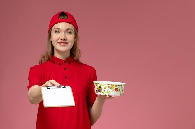 Vorderer blick junger weiblicher kurier in roter uniform und umhang, der lieferschüssel und notizblock auf hellrosa wand hält
