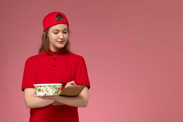 Vorderer blick junger weiblicher kurier in roter uniform und umhang, der lieferschüssel und notizblock hält, die notizen auf der rosa wand schreiben