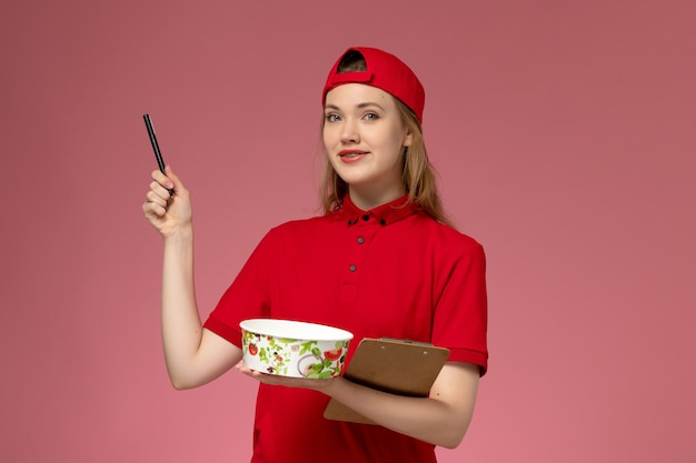 Vorderer blick junger weiblicher kurier in roter uniform und umhang, der lieferschüssel und notizblock mit stift rosa wand hält
