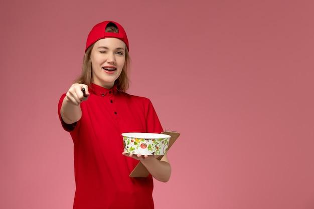 Vorderer blick junger weiblicher kurier in roter uniform und umhang, der lieferschüssel und notizblock mit stift zwinkert, der auf rosa wand zwinkert