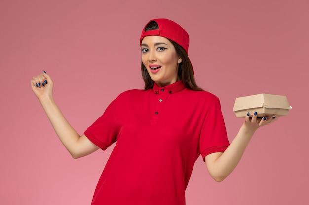 Vorderer blick junger weiblicher kurier in roter uniform und umhang mit wenig liefernahrungsmittelpaket auf ihren händen an der rosa wand
