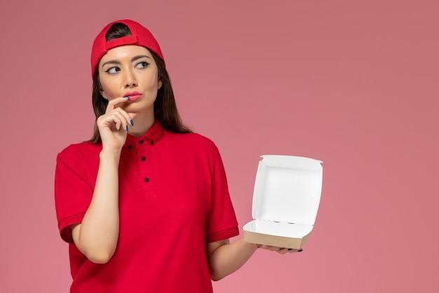 Vorderer blick junger weiblicher kurier in roter uniform und umhang mit wenig liefernahrungsmittelpaket auf ihren händen, die an hellrosa wand denken