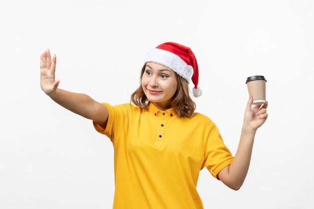 Vorderer blick junger weiblicher kurier mit kaffee auf weißer wanduniformdienstlieferung