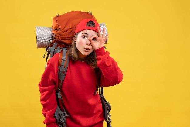 Vorderer blick junger weiblicher reisender mit rucksack, der okay zeichen zu ihrem auge hält