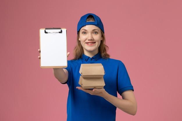 Vorderer blick weiblicher kurier im blauen uniformumhang, der kleine liefernahrungsmittelpakete und notizblock auf rosa hintergrundlieferdienstmitarbeiter-mädchenjob hält