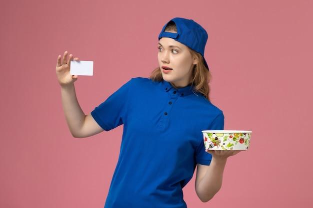 Vorderer blick weiblicher kurier in blauem uniformumhang, der lieferschüssel mit karte auf hellrosa wand hält, service delivery-mitarbeiter-arbeiterjob