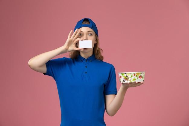 Vorderer blick weiblicher kurier in blauem uniformumhang, der lieferschüssel mit karte auf hellrosa wand hält, service delivery-mitarbeiterarbeitsjob