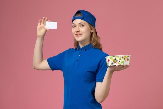 Vorderer blick weiblicher kurier in blauem uniformumhang, der lieferschüssel mit karte auf hellrosa wand hält, servicejoblieferungsmitarbeiter