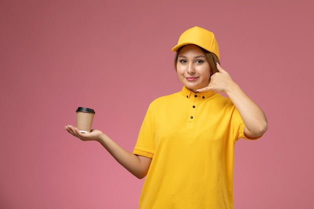 Vorderer blick weiblicher kurier in gelbem einheitlichem gelbem umhang, der braune kaffeetasse plastikplastik auf rosa schreibtischuniformlieferung weibliches mädchenfarbe hält
