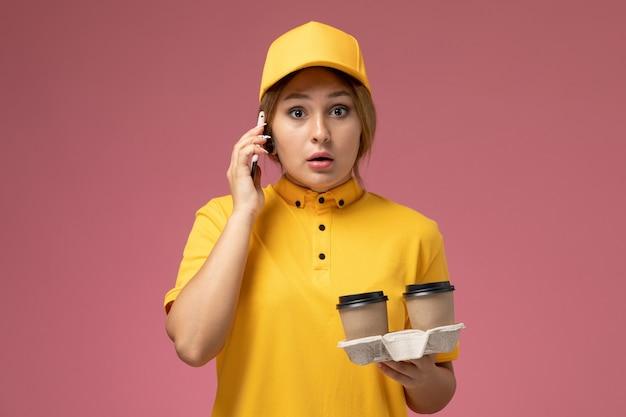 Vorderer blick weiblicher kurier in gelbem einheitlichem gelbem umhang, der kaffeetassen hält und am telefon auf rosa schreibtischuniformlieferarbeitsfarbjob spricht