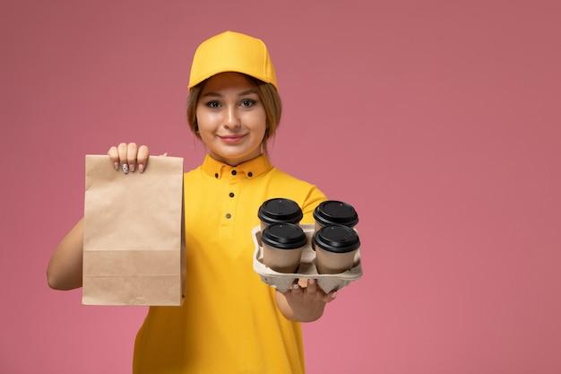 Vorderer blick weiblicher kurier in gelbem einheitlichem gelbem umhang, der kaffeetassen-lebensmittelpaket auf rosa hintergrunduniform-lieferarbeitsfarbe hält