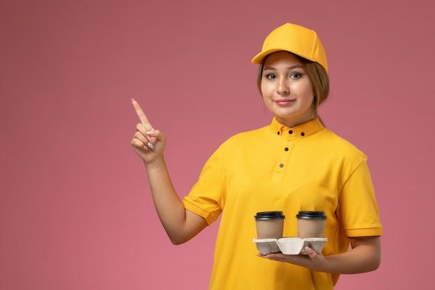 Vorderer blick weiblicher kurier in gelbem einheitlichem gelbem umhang, der kunststoffbraune kaffeetassen auf der weiblichen farbe der rosa hintergrunduniformlieferung hält