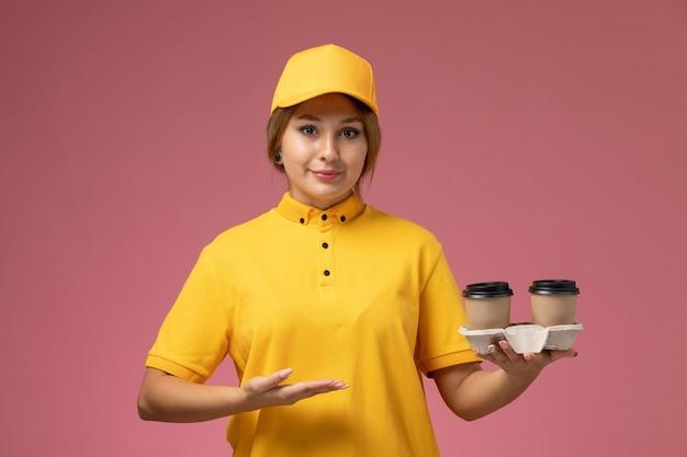 Vorderer blick weiblicher kurier in gelbem einheitlichem gelbem umhang, der kunststoffbraune kaffeetassen auf rosa schreibtischuniformlieferarbeitsfarbe weiblich hält