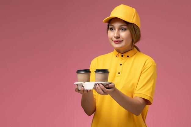 Vorderer blick weiblicher kurier in gelbem einheitlichem gelbem umhang, der kunststoffbraune kaffeetassen hält und sie auf der rosa schreibtischuniformzustellung weibliche farbe liefert