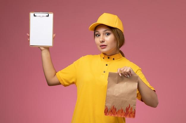 Vorderer blick weiblicher kurier in gelbem einheitlichem gelbem umhang, der lebensmittelpaket mit notizblock auf dem rosa hintergrunduniformlieferungsarbeitsfarbjob hält
