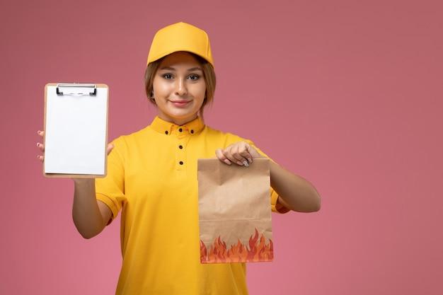 Vorderer blick weiblicher kurier in gelbem einheitlichem gelbem umhang, der lebensmittelpaket und notizblock auf dem rosa hintergrunduniformlieferungsarbeitsfarbjob hält