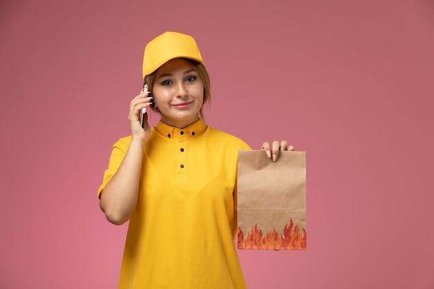 Vorderer blick weiblicher kurier in gelbem einheitlichem gelbem umhang, der lebensmittelpaket weiß spricht, das am telefon auf dem rosa schreibtischuniformlieferungsfarbjob spricht