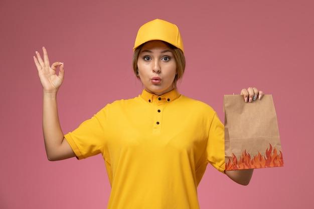 Vorderer blick weiblicher kurier in gelbem einheitlichem gelbem umhang, der lebensmittelverpackung auf dem rosa hintergrunduniformlieferungsarbeitsfarbjob hält