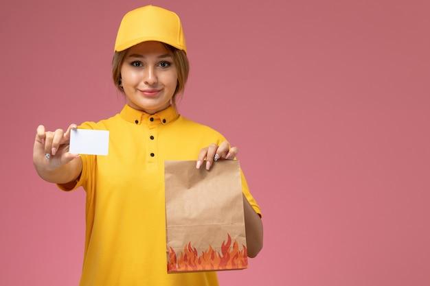 Vorderer blick weiblicher kurier in gelbem einheitlichem gelbem umhang, der lebensmittelverpackung hält weiße karte auf rosa schreibtischuniformlieferfarbauftrag hält